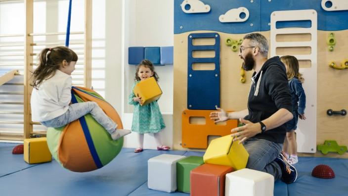 Kindergarten - Pre-school teacher and happy children playing in gym room in kindergarten model released Symbolfoto property released