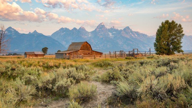 Famous John Moulton Barn stands in front of Teton Mountain Range on a cloudy day, Grand Tetons National Park, Teton Coun