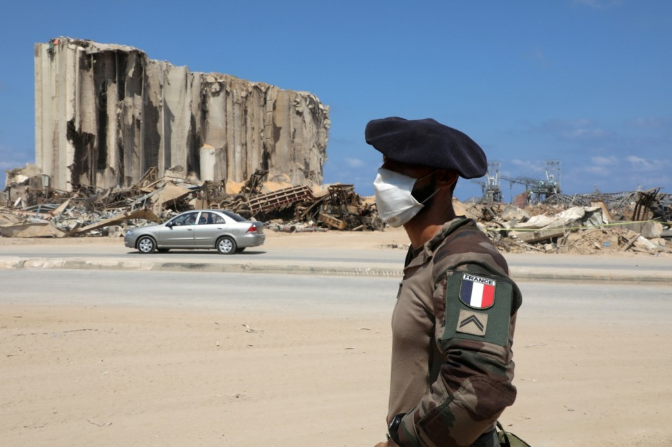 A member of the French military wears a face mask as he stands near the damaged grain silos during a joint effort with the Lebanese army to clear rubble from the port of Beirut following the explosion
