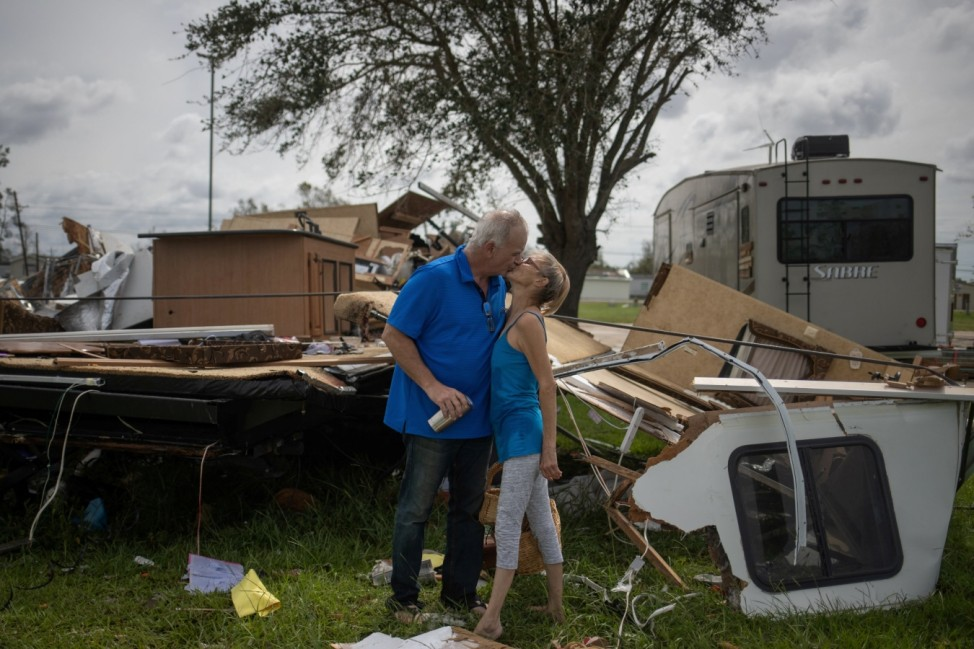 Couple kisses after returning to their destroyed resident in the aftermath of Hurricane Laura in Sulphur, Louisiana