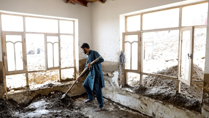 An Afghan man removes mud from a house after floods in Charikar, capital of Parwan province