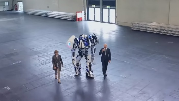 Computerspielmesse: Gamescom in Corona-Zeiten: In einem Eröffnungsvideo laufen die Kölner Oberbürgermeisterin Henriette Reker und Koelnmesse-Chef Gerald Böse mit einem Cosplayer im Roboterkostüm durch eine leere Messehalle.