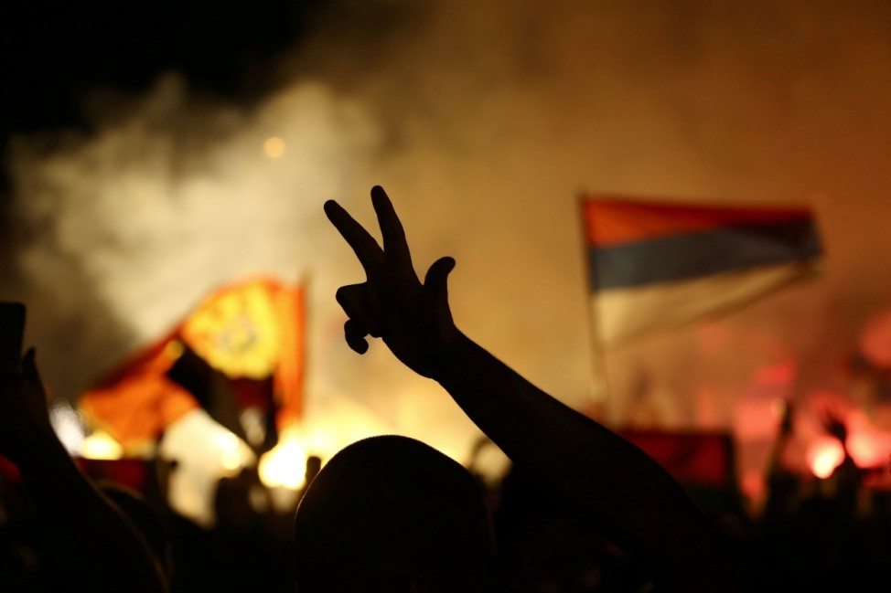 An opposition supporter shows a Serbian Orthodox three-finger sign during a celebration of the election victory in Podgorica