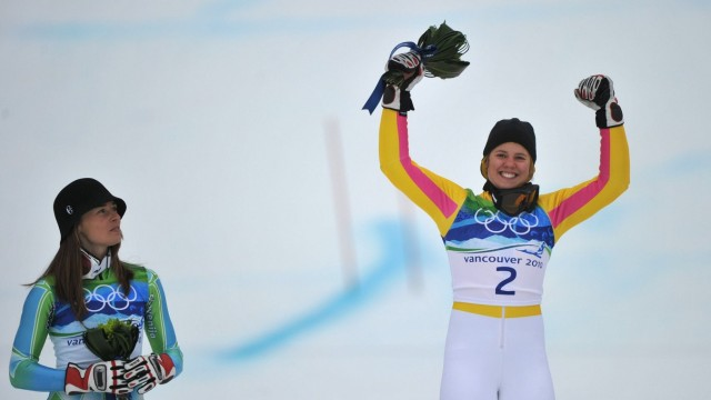 winner Germany s Viktoria Rebensburg (R) celebrates as Slovenia s Tina Maze watches on during the flower ceremony for t