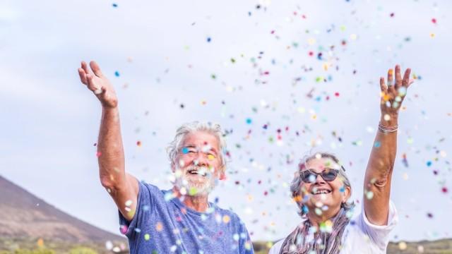 Happy senior couple celebrating with confetti outdoors model released Symbolfoto PUBLICATIONxINxGERxSUIxAUTxHUNxONLY SI