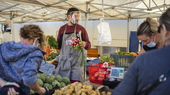 France - Open air market of Samatan during the COVID-19 health crisis. Greengrocer wearing a protective visor behind his