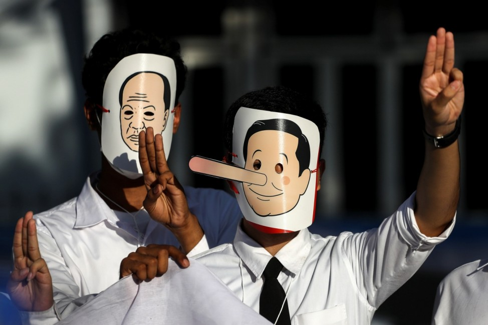 A pro-democracy student wearing a mask portraying Thailand's Prime Minister Prayuth Chan-ocha as Pinocchio does a three-fingers salute during a protest outside the Government House in Bangkok