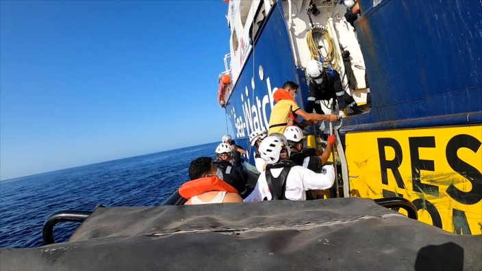 A rescued migrant enters the Sea- Watch 4 ship helped by a rescue team, at sea off the coast of Libya