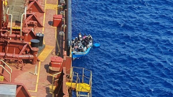 FILE PHOTO: Migrants sit in a boat alongside the Maersk Etienne tanker off the coast of Malta