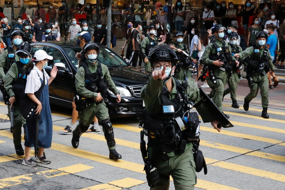 Riot police chase pro-democracy protesters during a demonstration oppose postponed elections, in Hong Kong