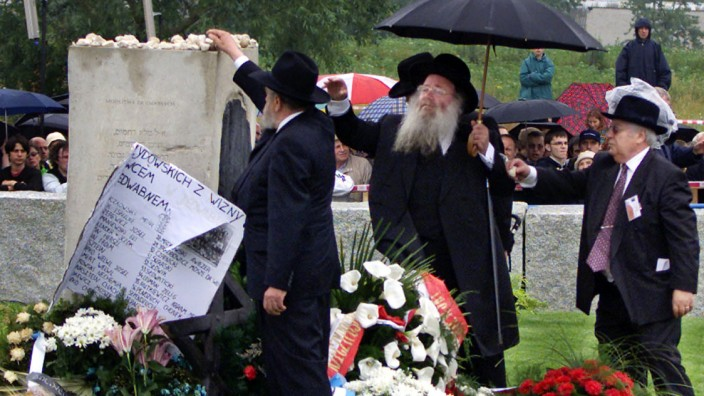 A GROUP OF RABBIS PLACES STONES ON TOP OF THE MONUMENT IN JEDWABNE