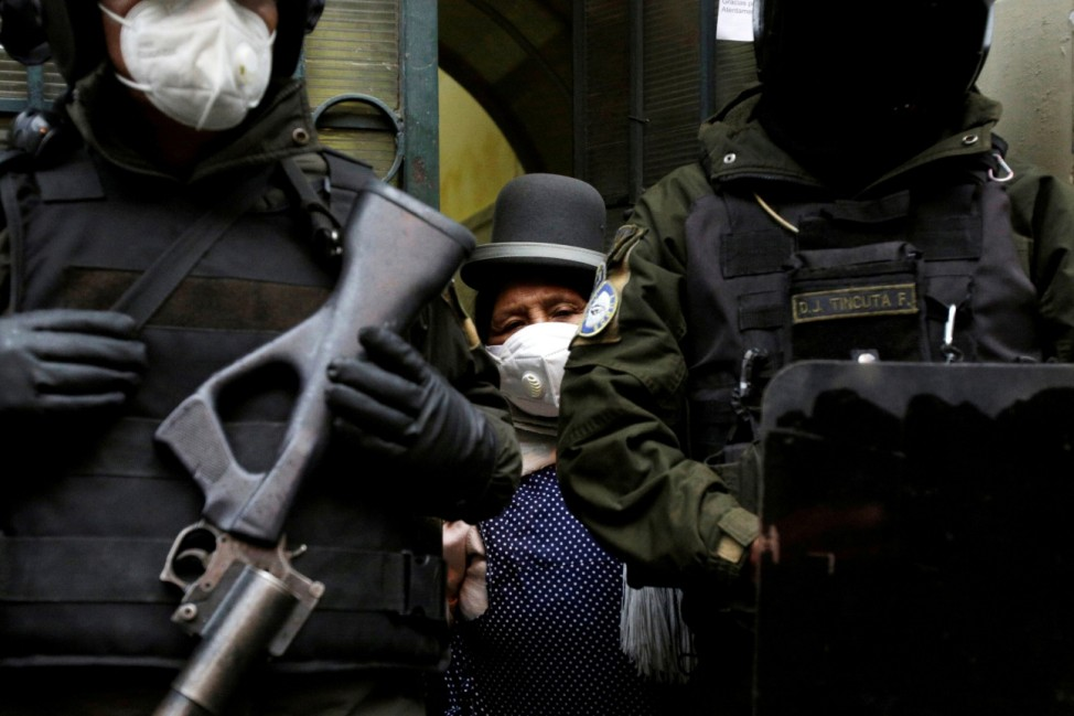 A woman stands behind riot police outside a court of justice before an appeal filed by former president Evo Morales, in La Paz