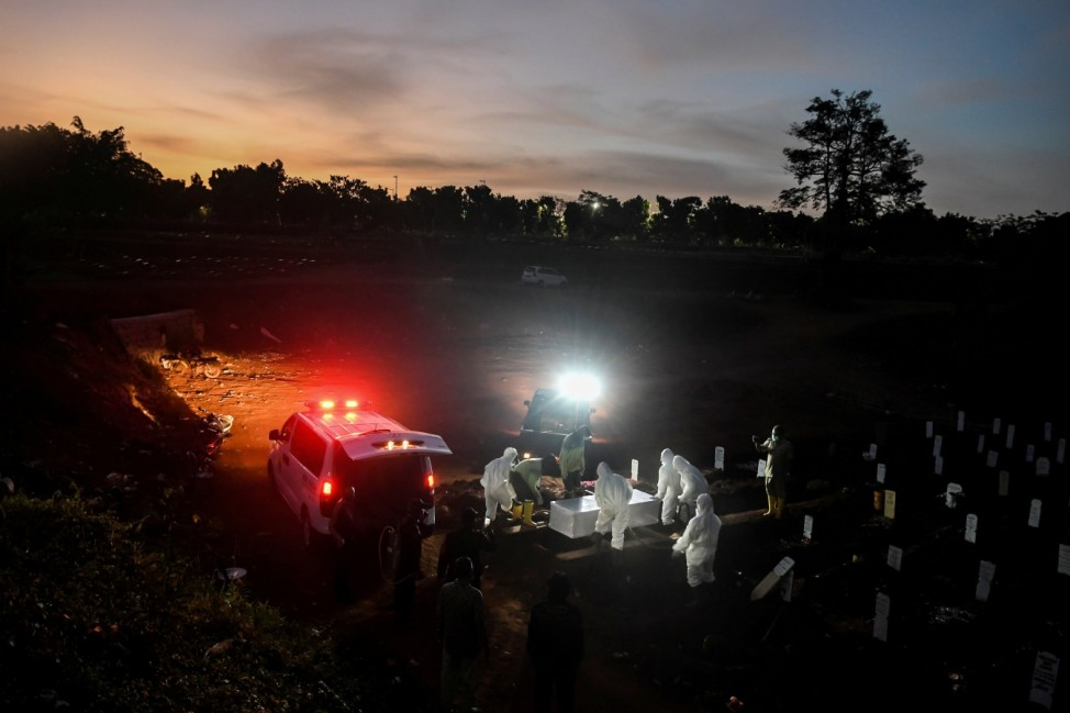 Workers wearing protective suits bury a coronavirus disease (COVID-19) victim at Pondok Ranggon cemetery complex in Jakarta