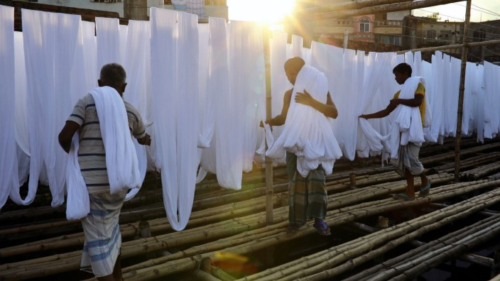 Workers sort sun-dried fabrics in a dyeing factory in Narayanganj