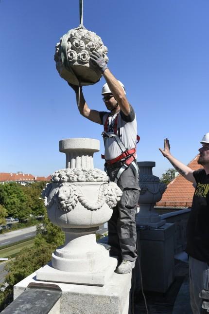 Rekonstruktion: Schön vorsichtig: Ein Arbeiter montiert am Mittwoch den Nachbau einer historischen Ziervase auf dem Dach des Botanischen Instituts.