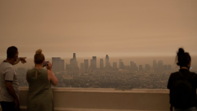 People watch as tick smoke from the Bobcat fire moves through Los Angeles