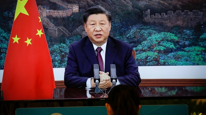Journalist sits next to a screen showing Chinese President Xi Jinping delivering a speech via video for the opening ceremony of the 2020 China International Fair for Trade in Servic