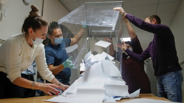 Members of a local electoral commission empty a ballot box to start counting ballots at a polling station after polls closed for municipal elections in Tomsk
