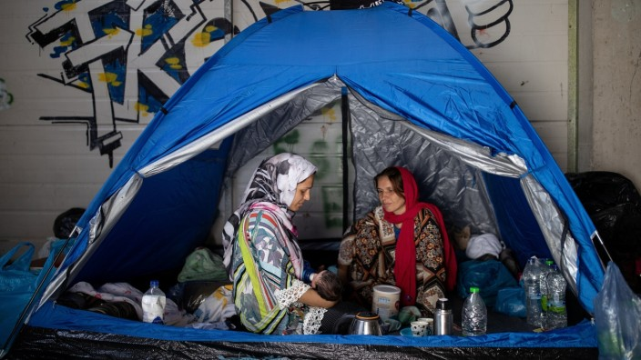 A woman gives milk to her newborn baby as refugees and migrants from the destroyed Moria camp find shelter in a warehouse near a new temporary camp, on the island of Lesbos