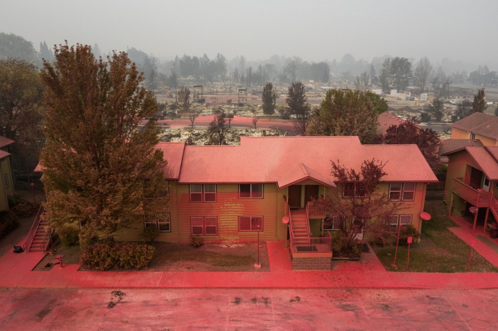 Red fire retardant blankets a residential building in the aftermath of the Almeda fire in Talent, Oregon