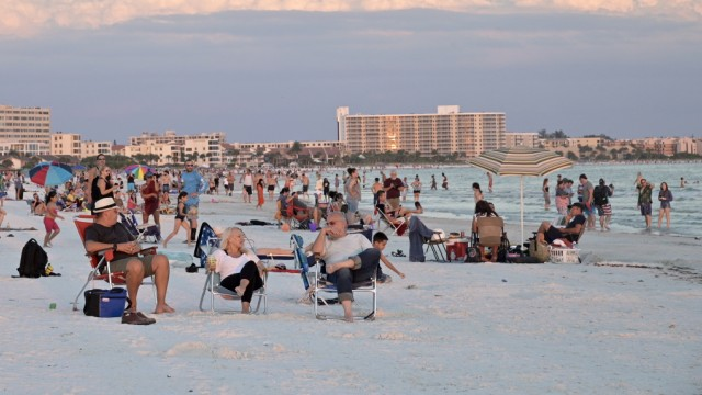Visitors enjoy Siesta Key Beach as the sun sets over the Gulf of Mexico,