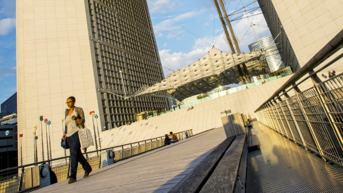 Woman walking below La Grande Arche de la Defense Paris France PUBLICATIONxINxGERxSUIxAUTxONLY Copy