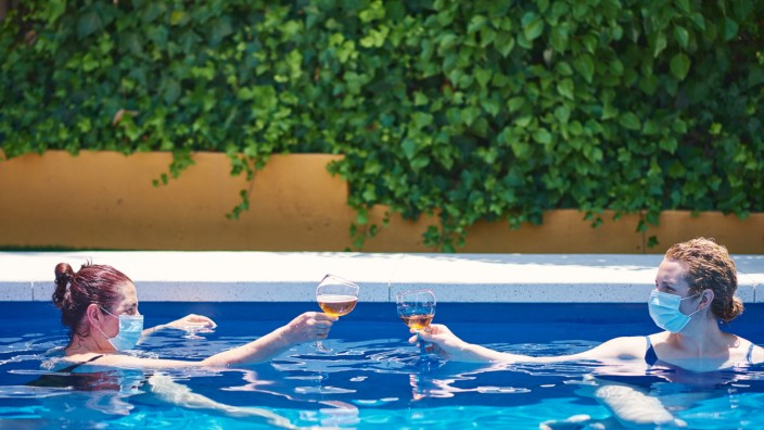 Two women toast in a pool. They wear masks to prevent the spread of the virus. Córdoba, AL, Spain PUBLICATIONxINxGERxSUI