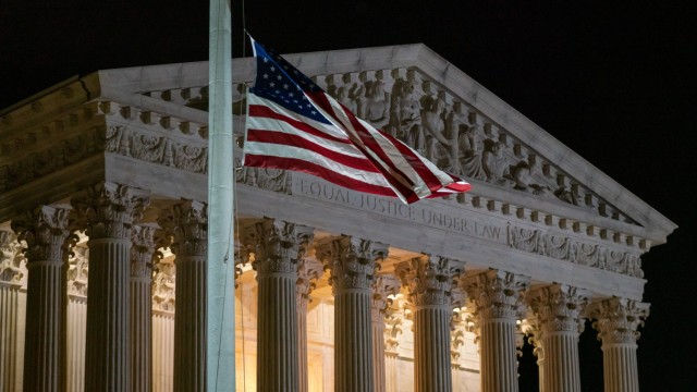 Flags fly at half-staff as people pay respects for Associate Supreme Court Justice Ruth Bader Ginsburg at the steps of