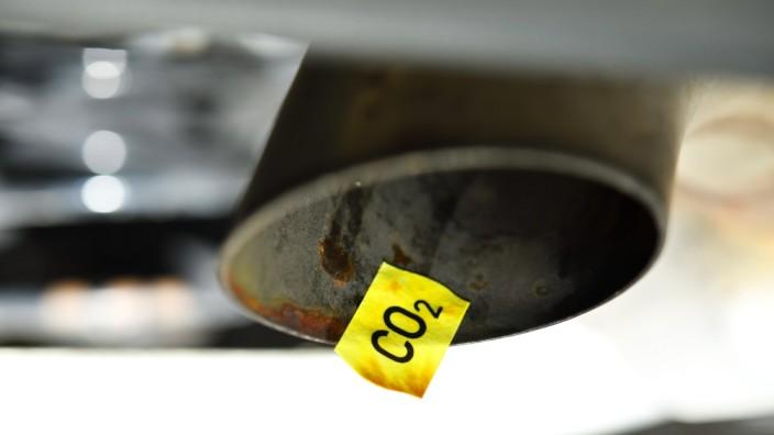CO2-Preisschild auf dem Auspuff eines Autos, CO2-Steuer *** CO2 price tag on the exhaust of a car, CO2 tax