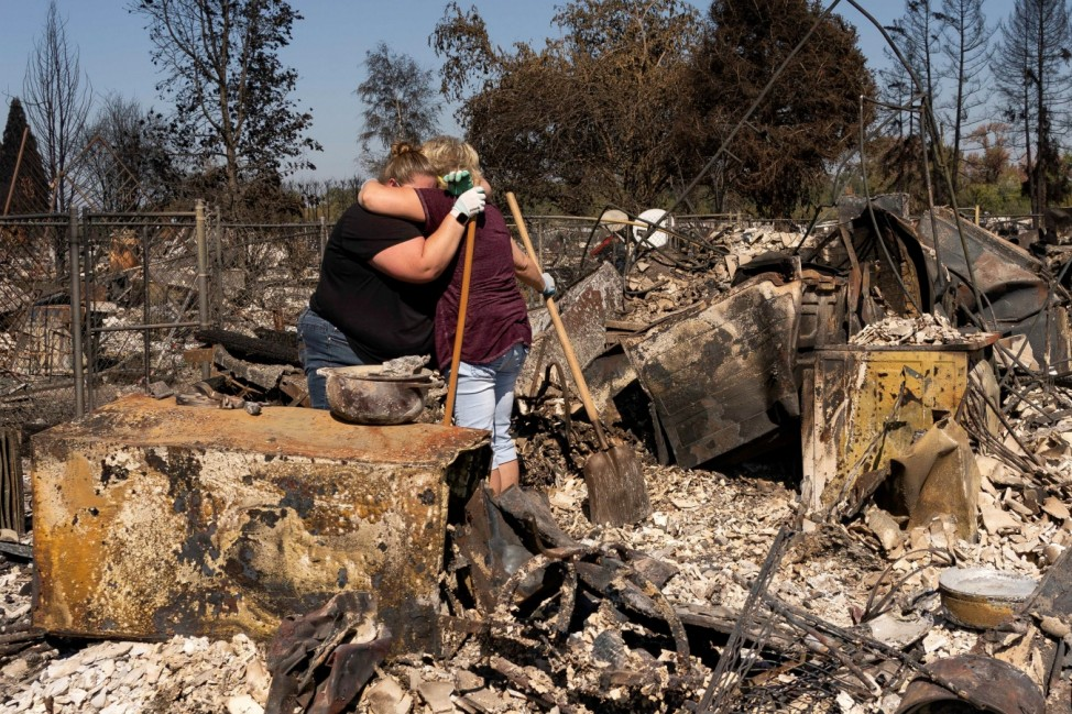 Destruction after wildfires in Oregon Stephanie Adams embraces her mother, April Beard, while searching through the remnants of Adams's destroyed home for mementos from her significant other, who passed away late last year, in a neighborhood severely damaged by wildfire in Medford, Oregon, U.S. September 20, 2020. REUTERS/David Ryder TPX IMAGES OF THE DAY