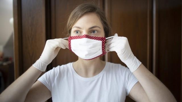 Thema: Junge Frau zieht einen Mundschutz an und traegt Handschuhen. Radevormwald Deutschland *** Topic Young woman puts