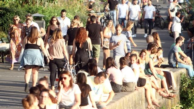 Großer Personenandrang an Sonnenhungrigen, die die Abendsonne und den warmen Sommertag auf der Uferpromenade am Mainufer