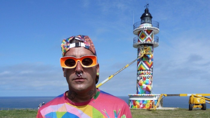 Spanish artist Okuda San Miguel poses next to his mural on the Ajo lighthouse in Bareyo, Cantabria, northern Spain. Okud