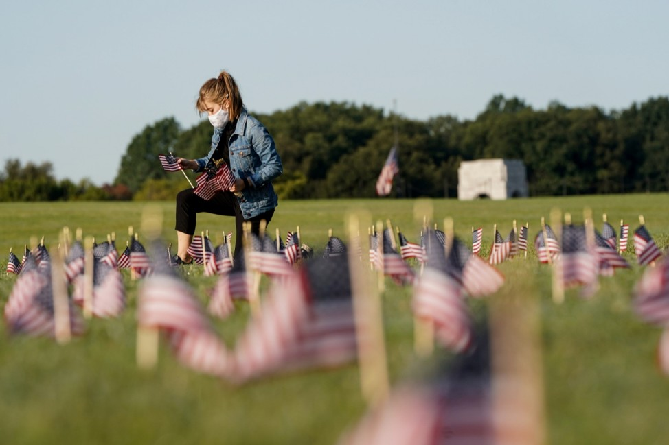 American flags representing 200,000 lives lost due to coronavirus are placed on National Mall in Washington