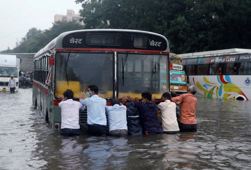People push a bus through a waterlogged road after heavy rainfall in Mumbai