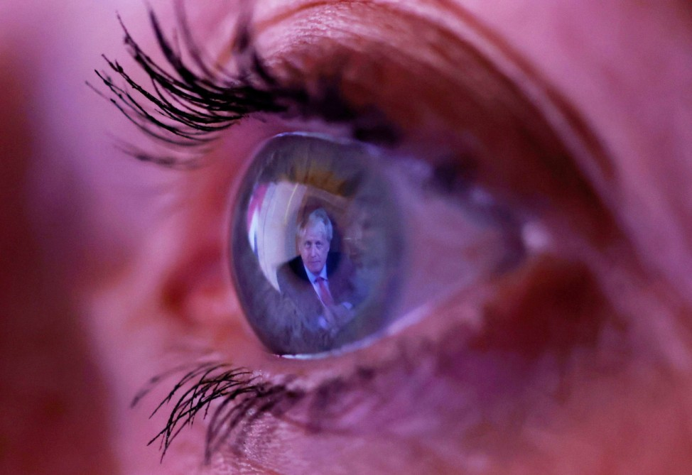 Britain's Prime Minister Boris Johnson is reflected in a woman's eye as she watches his address to the nation following the outbreak of the coronavirus disease (COVID-19) in Manchester, Britain