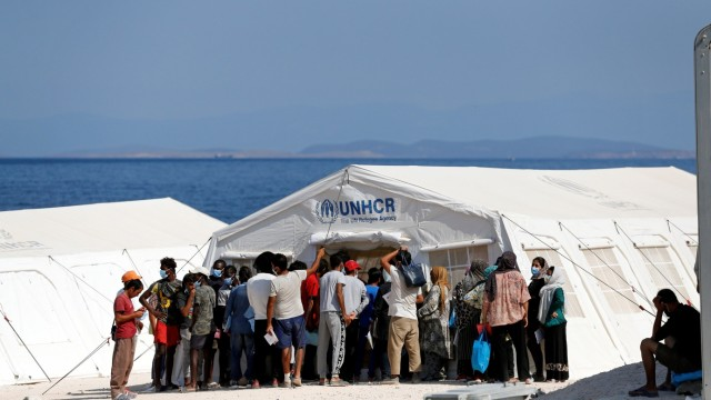 Refugees and migrants from the destroyed Moria camp gather outside a UNHCR tent at a new temporary camp on the island of Lesbos