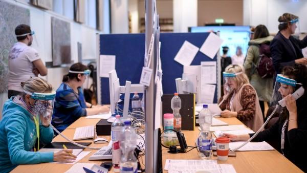 Berlin: Mitarbeiter des Gesundheitsamtes Mitte mit Gesichtsschutzschirm telefonieren im Lagezentrum des Gesundheitsamt Mitte.