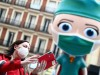 A woman wearing a protective face mask takes a selfie next to an oversized model of a health worker in Madrid