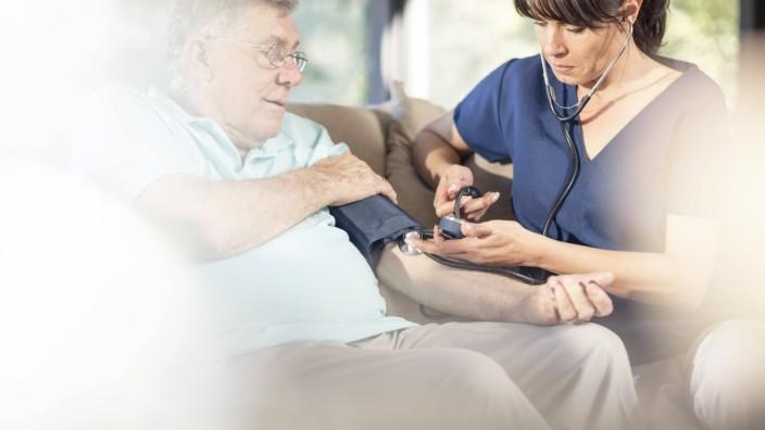 Nurse taking blood pressure of senior patient at home model released Symbolfoto property released P