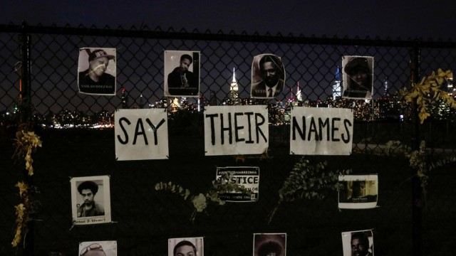 Pictures are seen placed at a makeshift memorial for victims of racial injustice, following the announcement of a single indictment in the Breonna Taylor case, in the Brooklyn borough of New York City