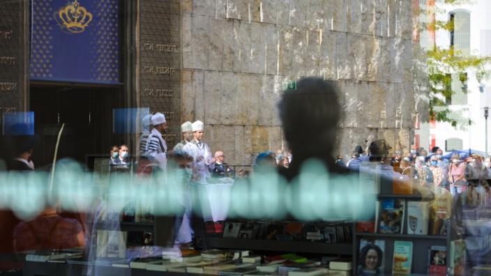 Juden in Deutschland: Im Fenster spiegelt sich, wie die jüdische Gemeinde in München das Neujahrsfest Rosch Haschana vor der Ohel-Jakob-Synagoge feiert.