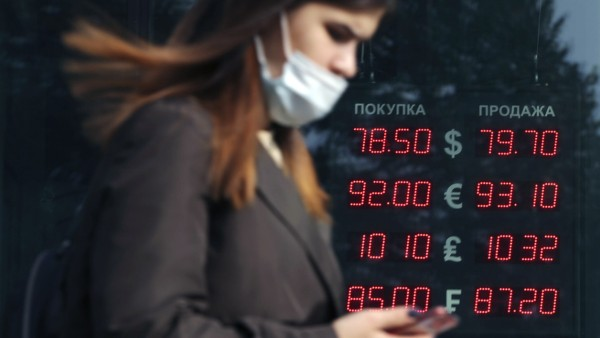 MOSCOW, RUSSIA - SEPTEMBER 29, 2020: A woman walks past a currency exchange office.