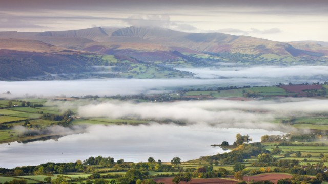 WALES Pen Y Fan rises above a mist shrouded landscape near Llangorse Lake Brecon Beacons National P
