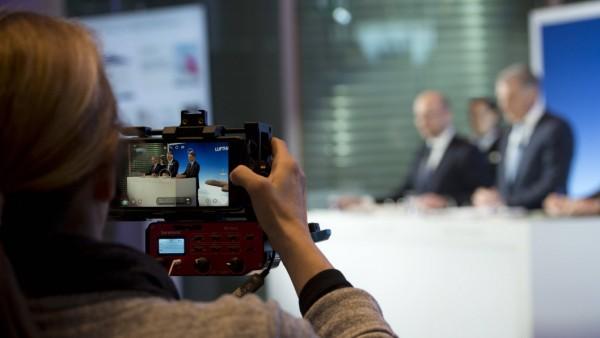 Eine Kamerafrau filmt die Pressekonferenz Symbolfoto Feature Randmotiv Bilanzpressekonferenz der