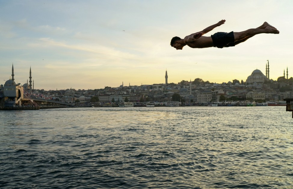 A boy jumps into the sea at Karakoy district in Istanbul