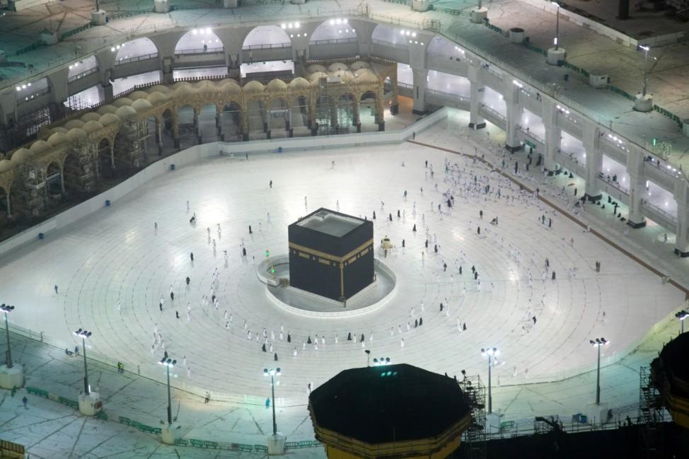 The first group of Muslims, allowed in the mosque compound by appointment, practice social distancing, as they perform Umrah in the Grand Mosque, after Saudi authorities ease coronavirus disease (COVID-19) restrictions, in the holy city of Mecca