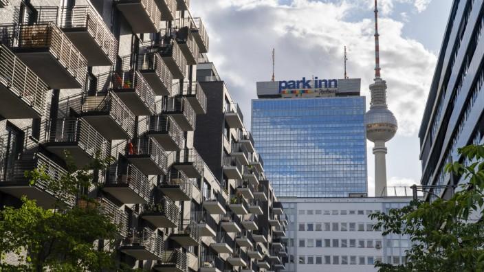 Das park inn Hotel und der Fernsehturm am Alexanderplatz in Berlin-Mitte. Im Vordergrund links ein Wohnhaus und rechts e