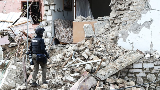 STEPANAKERT, NAGORNO-KARABAKH - OCTOBER 8, 2020: A journalist by a building damaged in a shelling attack. The conflict