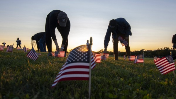 Covid Memorial Project volunteers plant 20,000 American flags at sunset on the National Mall to represent the 200,000 A